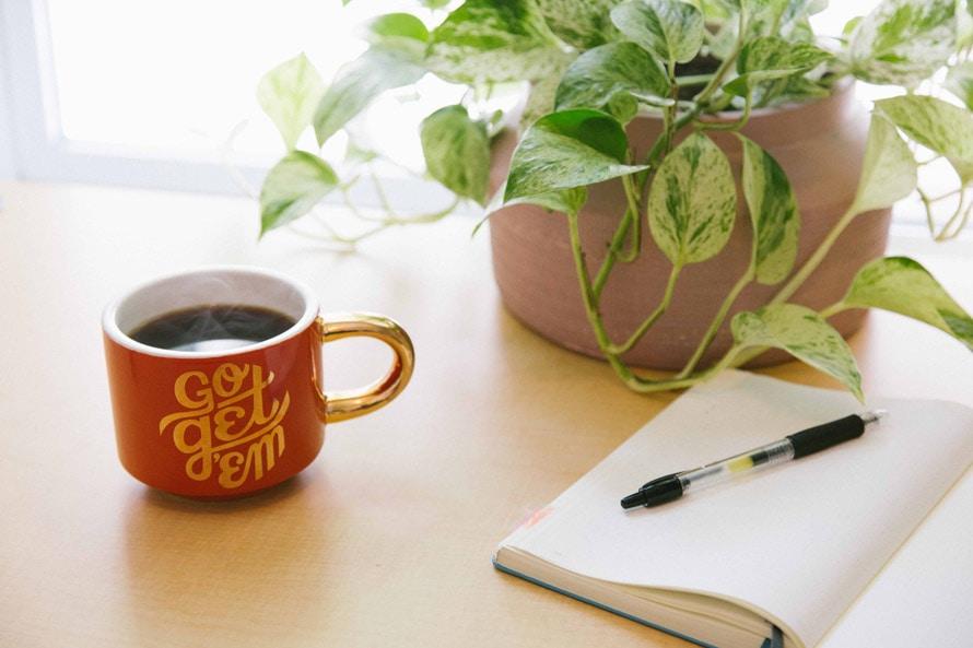 """Desk top with """"Go Get Em"""" Coffee Mug and Notebook"""